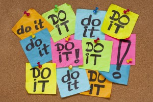Fight procrastination concept - do it phrase on color sticky notes posted on a cork bulletin board