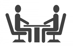 Clip art of two persons facing each other at table