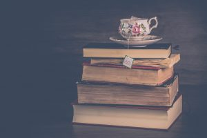 Photo of a stack of books topped with a cup of tea