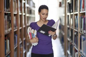 Woman with books in library stacks